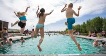 Barn som hoppar i en simbassäng