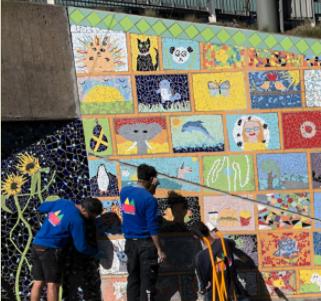 Bild på personer som sätter upp mosaikbilder på tunnelväggarna.